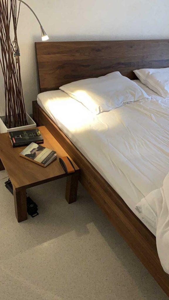 Dunkles Holzbet mit Nachttisch