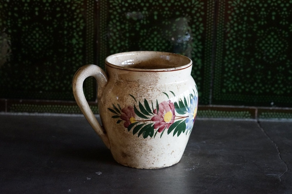 antiker Krug aus Keramik. Bemalt mit Blumenmotiven